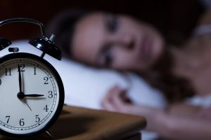 woman with insomnia starting at alarm clock on table